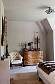Old domestic appliances on Baroque chest of drawers and antique armchair in attic bedroom