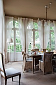 Wicker chairs around breakfast table in front of arched French windows in dining room with traditional ambiance