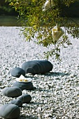Summer party on river bank: rocks painted grey with stripes as decoration on pebble shore