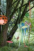 Drahtstuhl mit bunten Dekobändern am Baum hängend