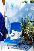 Bright blue sun lounger in front of batik fabric screen and Mediterranean plants in terracotta pots