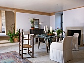 Dining table and chairs with pale covers in front of fireplace in rustic interior