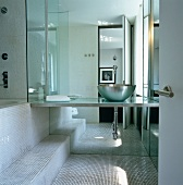 Modern bathroom with mosaic tiles and washstand with metal basin in front of mirrored wall