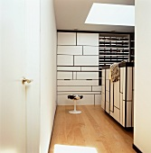 Partially open-fronted fitted wardrobe and stool with animal-skin cover in designer dressing room
