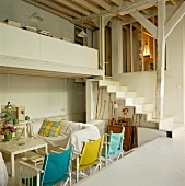 Couch and wooden chairs with coloured canvas covers around table below gallery with staircase