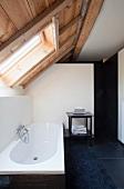 Designerbad in renoviertem Dachgeschoss - schwarze Bodenfliesen und Badematte vor Badewanne unter Dachfenster