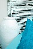 Pale ceramic floor vase and blue cushion against panel of sticks