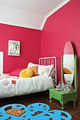 Colourful teenager's bedroom with painted walls and vintage dressing table next to bed