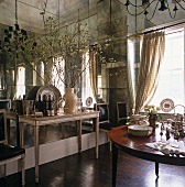 Neo-classical console table against wall with mirrored panels in elegant dining room