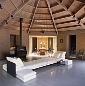 Sofa combination in polygonal room with tented wooden ceiling and view of dining area