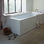 Designer bathtub in front of window and pebbles on concrete floor