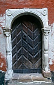 Stone portal with old wooden door in red lime-washed walls