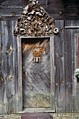 Old wooden door of old wooden house with weathered, carved lintel