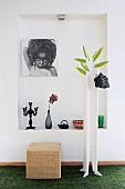 Home-made coat rack and rattan stool in front of photograph hanging in niche