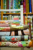 Rolls of patterned fabric on chair in front of shelves of various fabrics