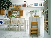 Dining room with white chairs and monolithic counter on white tiled floor