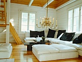 White corner couch with black cushions and chandelier in corner of living room in wooden house