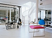 Modern chair with colourful upholstery and free-standing staircase in home gym