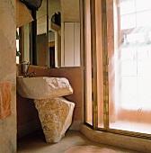 Künstlerisch gestalteter Waschtisch aus Steinfelsen unter Spiegelschrank