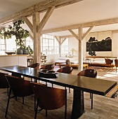 Dark wood dining table and designer shell chairs in loft-style interior