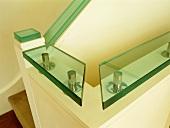 Flat, glass handrail above white, wooden balustrade