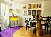 Dining table and black chairs with vintage jukebox in corner