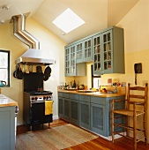 Country kitchen with blue wooden units and free-standing cooker with extractor hood