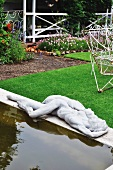 Pond with concrete surround and statue in tidy garden