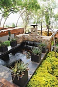 Large stone flags surrounding pond provide room for potted plants
