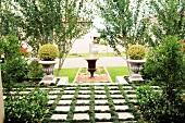 Amphoren im Antikstil vor Pappelreihe als Gestaltungselemente in einem Vorgarten; im Vordergrund mit breiter Rasenfuge verlegte Betonplatten