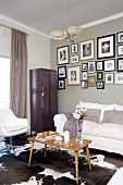 Corner of living room with white seating, old locker and framed photos on wall