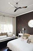 Dark bedroom walls and floor provide the perfect backdrop for white bed linen