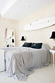 Double bed with grey bed linen and surfboard on wall in bedroom