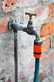 A garden hose attached to a tap on a house wall