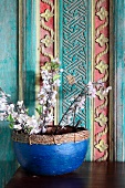 Flowering twigs in blue pot against painted and carved wooden wall