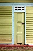 Front door of yellow-painted wooden house