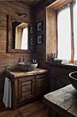 Helles, holzverkleidetes Badezimmer mit rustikalem Waschtisch und Stein-Waschschüssel; an der Wand ein quadratischer Badezimmerspiegel