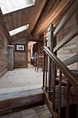 Holzverkleideter Flur mit Dachschräge und Dachfenster; im Vordergrund der Treppenabgang aus Holz