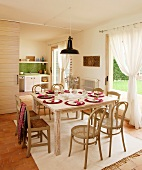 Bentwood chairs with cane seats and simple, rush-bottom chairs at festively set table in front of draped curtains