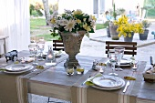 Festively set table on terrace with view of courtyard