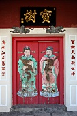 Rotes Haustor bemalt mit Figurenmotiven und asiatischen Schriftzeichen