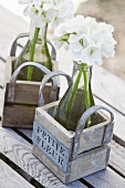 White flowers in water-filled bottles in wooden crates with handles