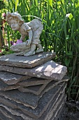 Stone figurine on stack of stone slabs in garden