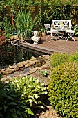 Small pond and wooden deck with bust next to table and garden chairs
