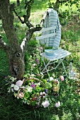 Basket of garden flowers on lawn and chair beneath tree