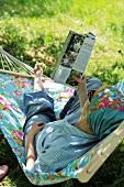 Schattiges Gartenplätzchen - Frau lesend in einer Hängematte