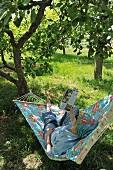 Shady spot in garden - woman reading in hammock