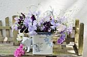 Garden flowers in ceramic pot and cow creamer on garden bench
