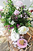 Bouquet of garden flowers in vase and slice of cake on rusty garden table