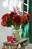 Flamboyant summer bouquet next to drinks on rustic wooden stool